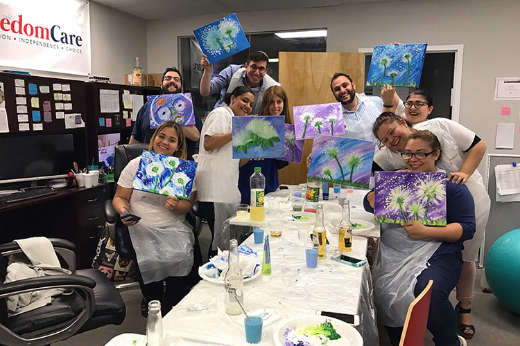 FreedomCare workers showing the paintings they've done