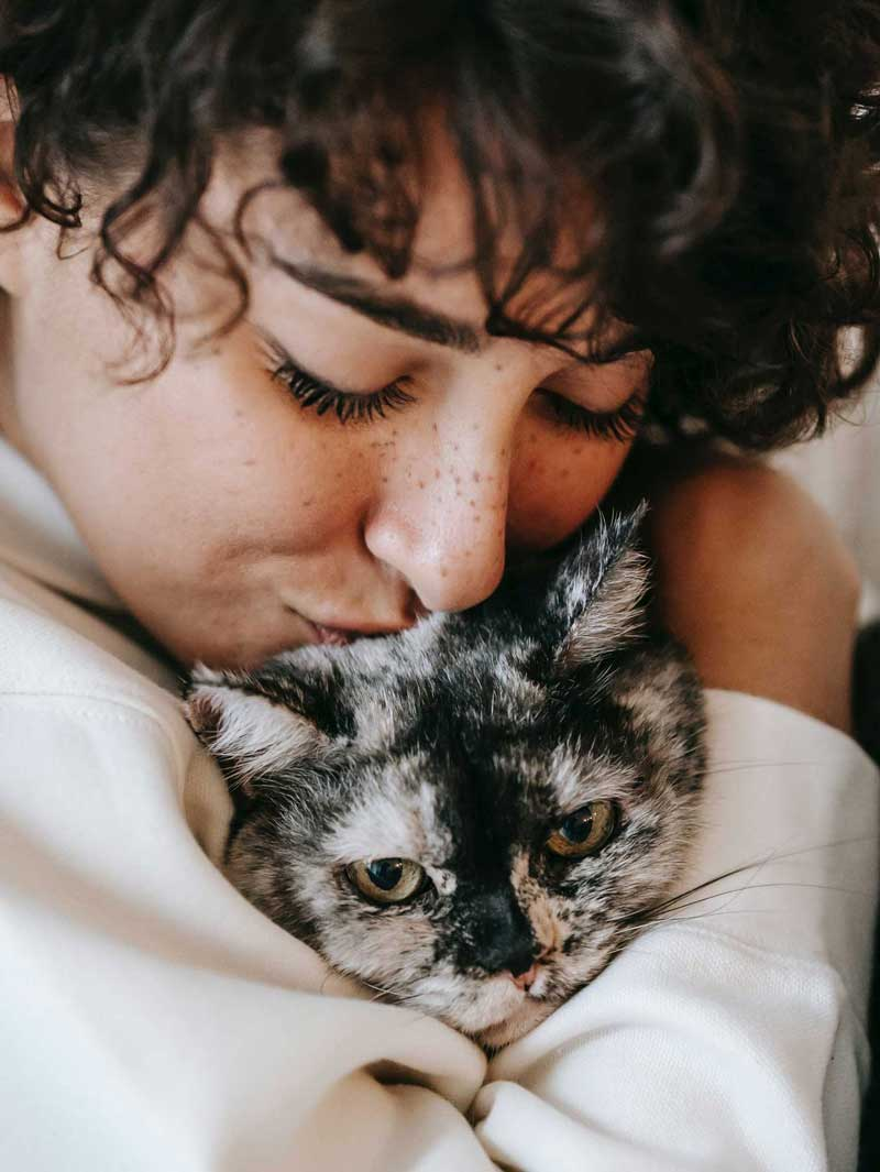 An image of a woman hugging a cat