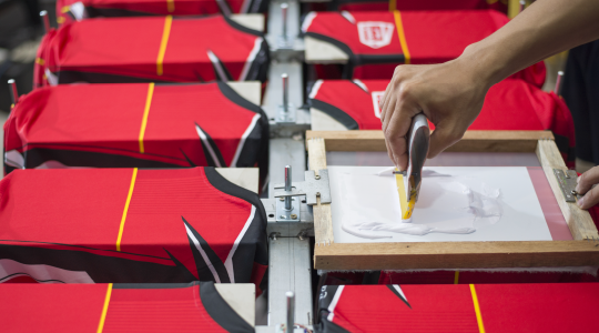 A screen printing factory line with jerseys