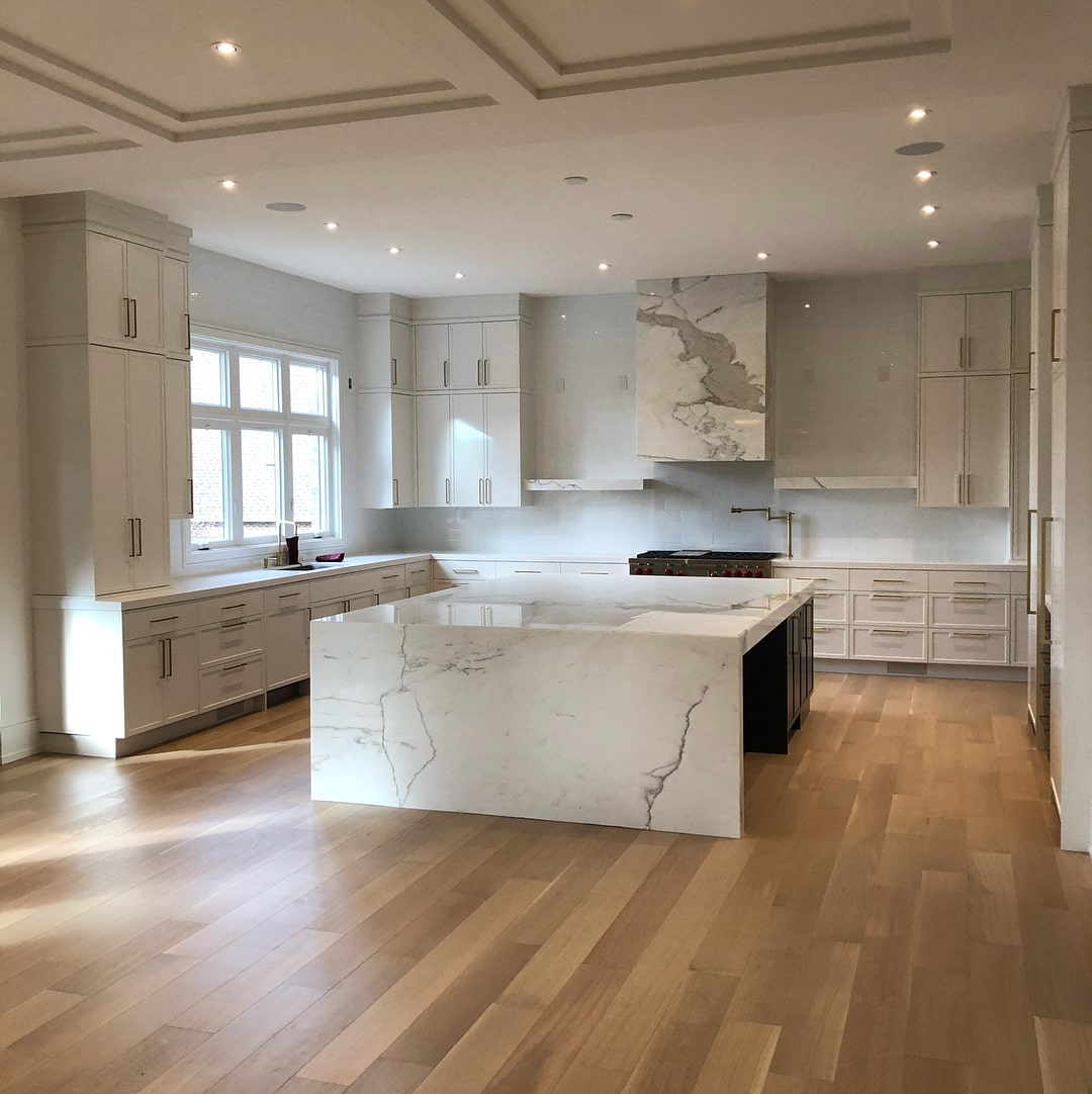 classic white kitchen with a large marble island