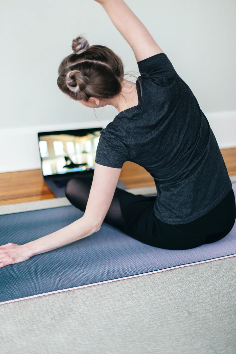 Young woman fitness instructor teaches a virtual fitness class from her home.