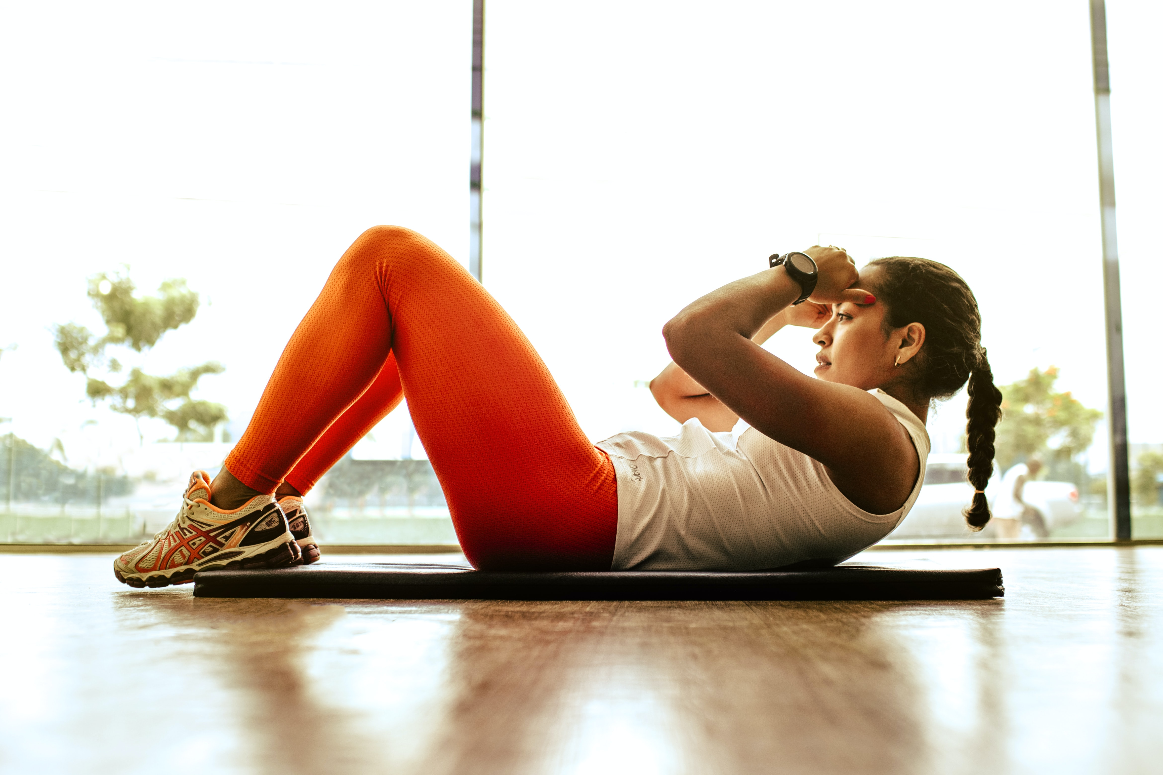 Woman does crunches on her yoga mat as a part of your online fitness class.