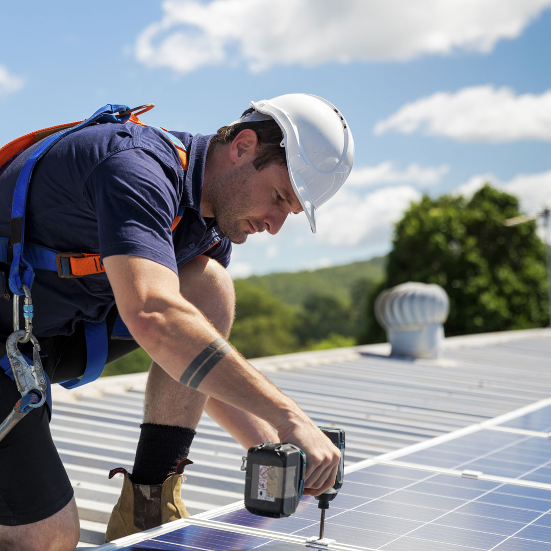 A tradesman installing solar panels on the roof of a building