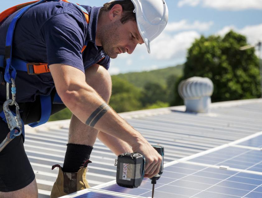 A solar installer installing panels onto a roof