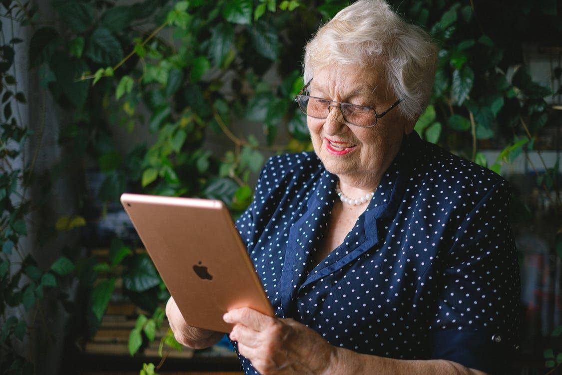 Aged cheerful female smiling and using contemporary tablet while talking on tablet in living room with green plant