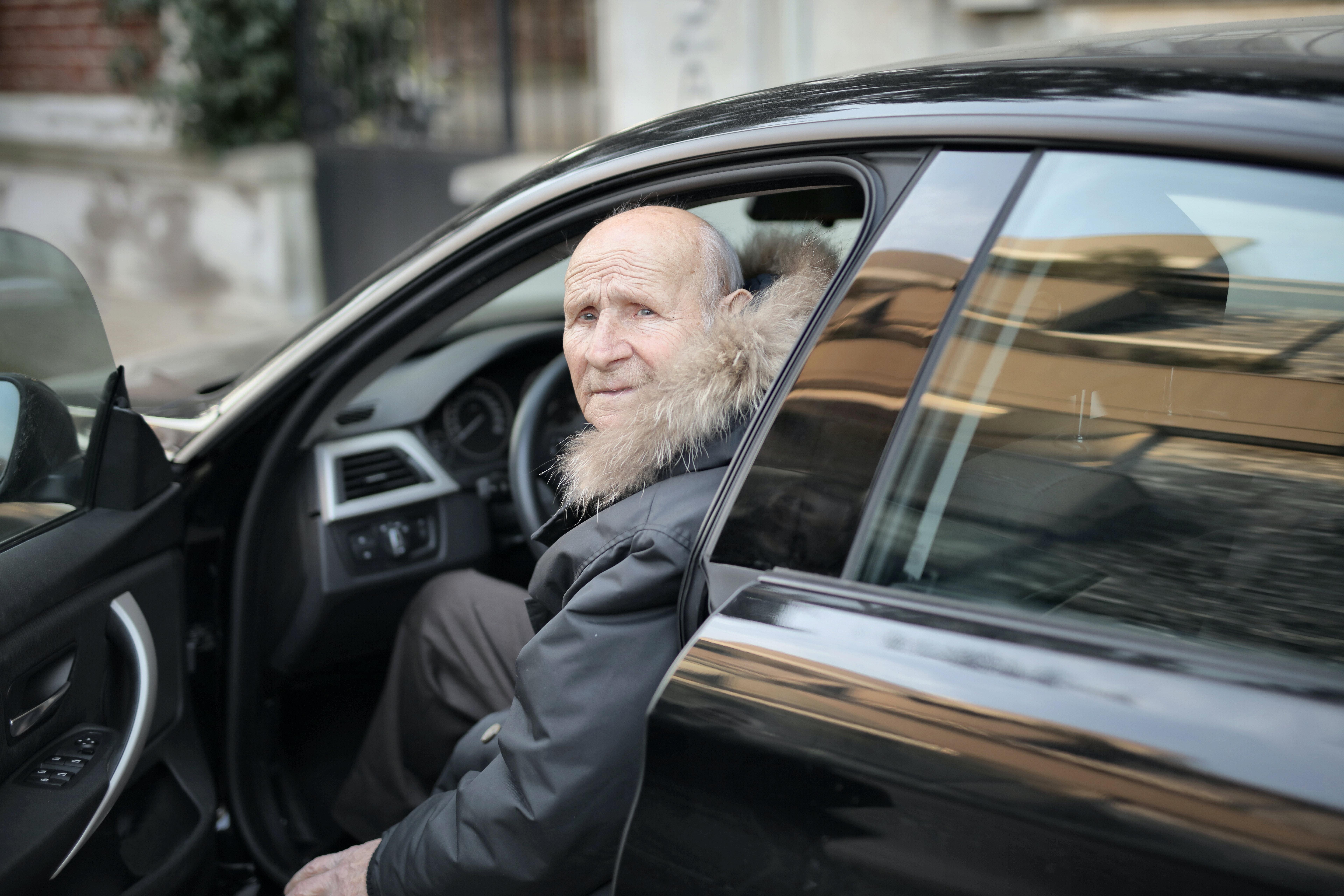 old man driving a black car