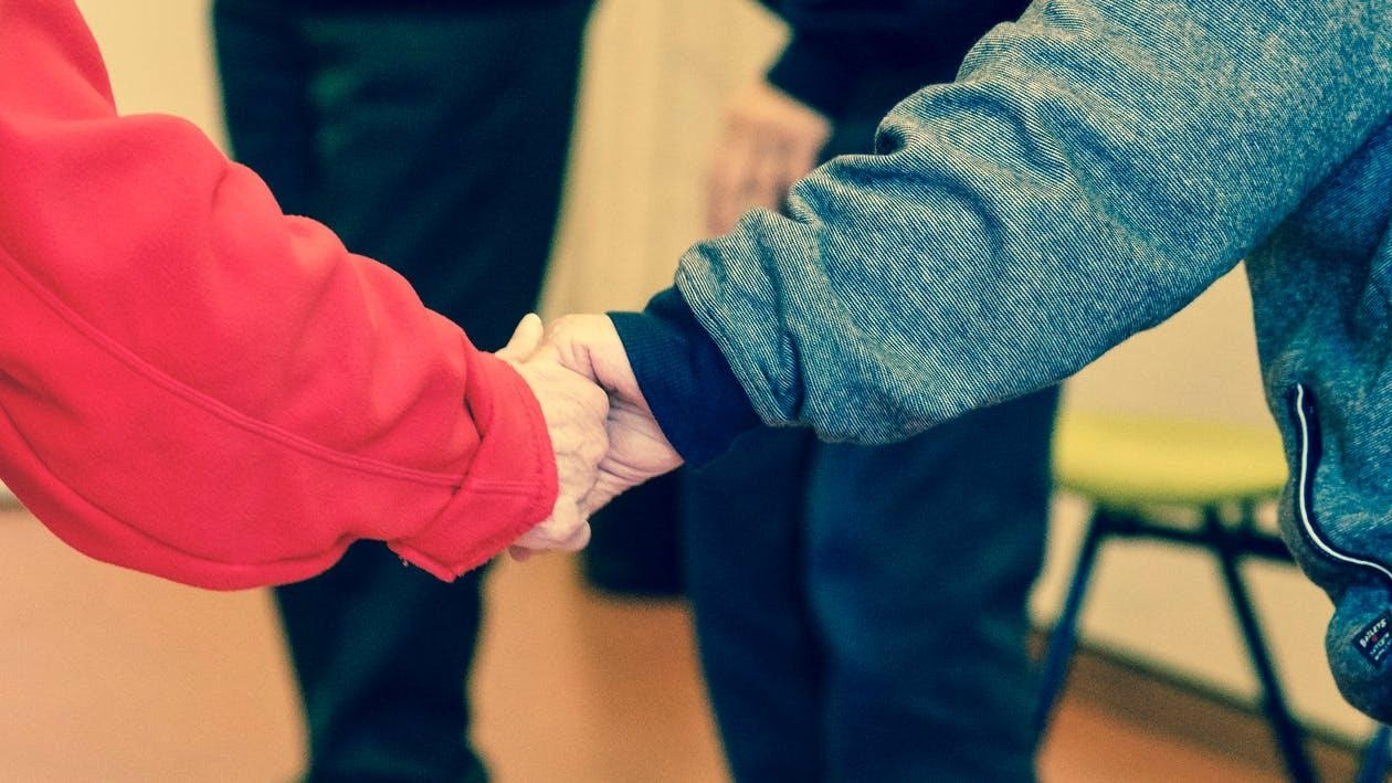 2 Persons  Holding Their Hands