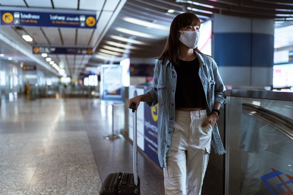Woman With a Face Mask Holding her Luggage