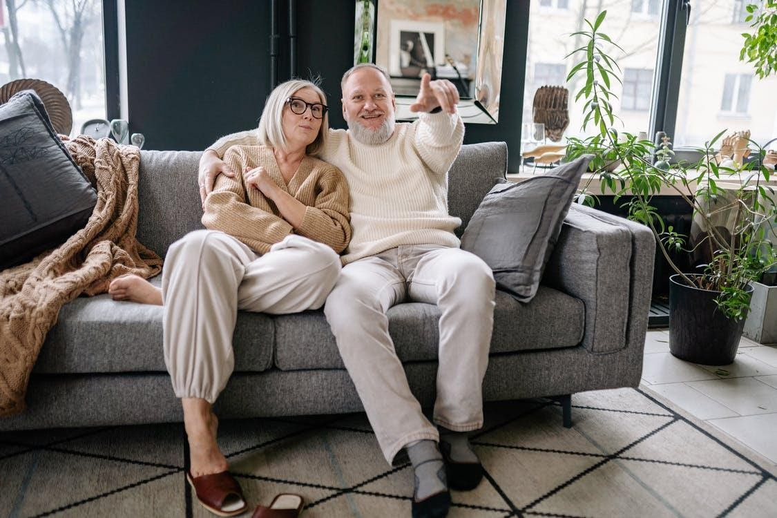 Woman in Beige Long Sleeve Shirt Sitting on Gray Couch