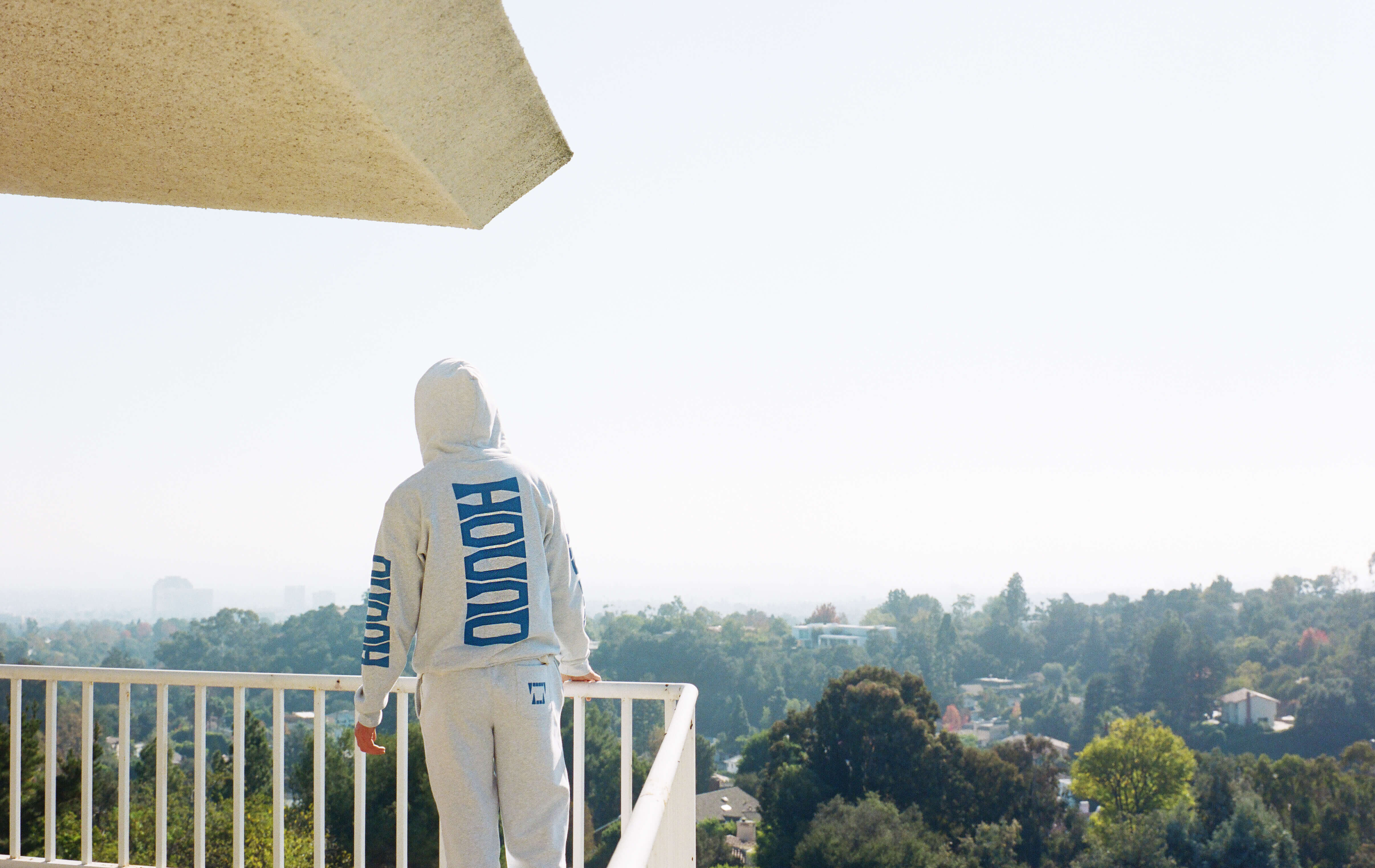 A person wearing a Hound hoodie looks off into the distance from a balcony