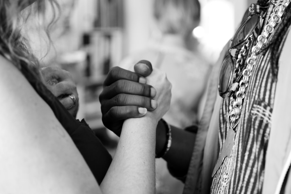 grayscale photo of man and woman holding their hands
