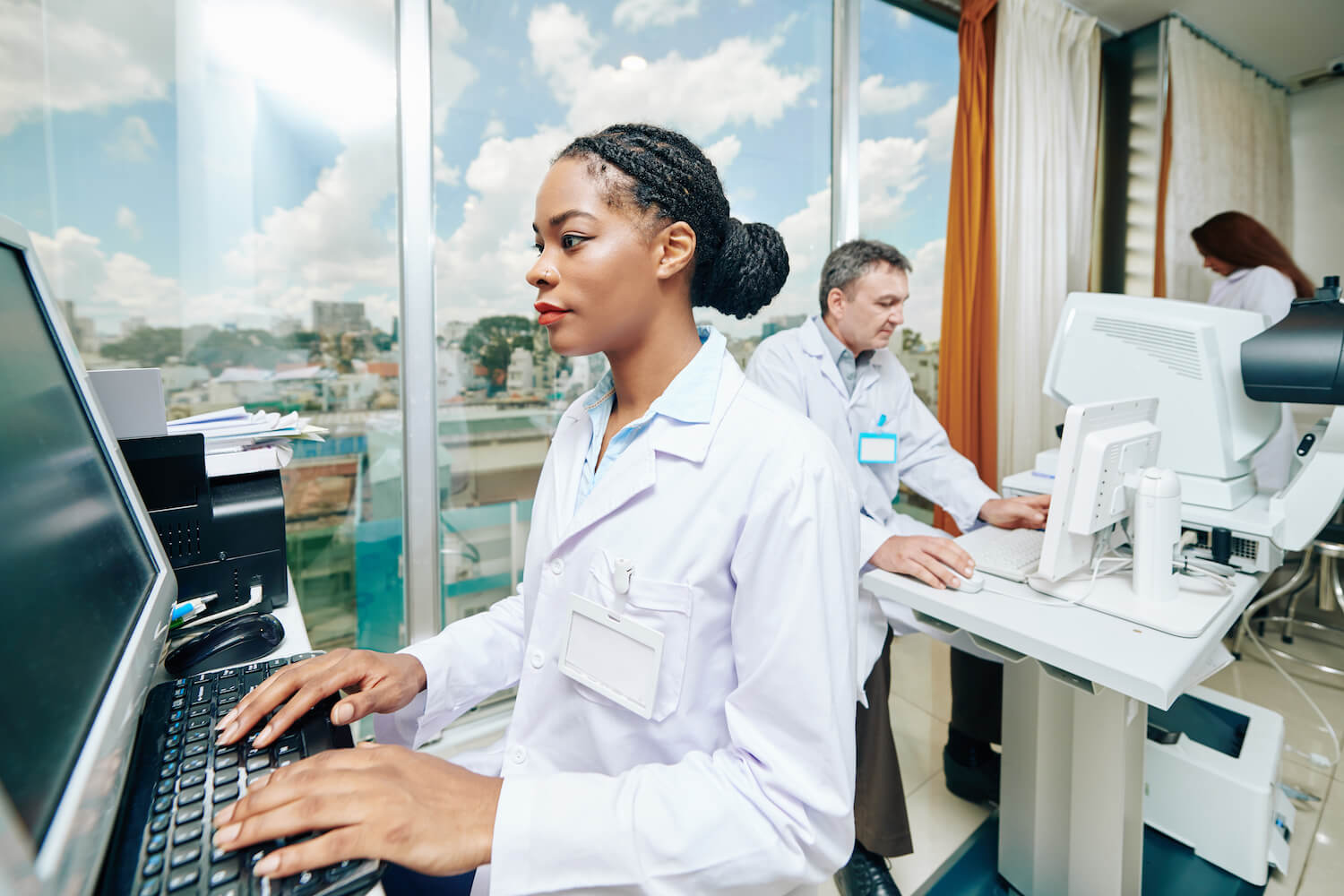 A women doctor typing on a computer with other staff in the background.