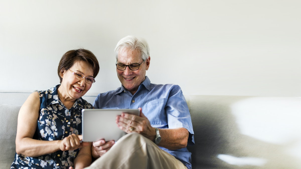 Elderly couple sat on sofa together smiling and looking at a tablet