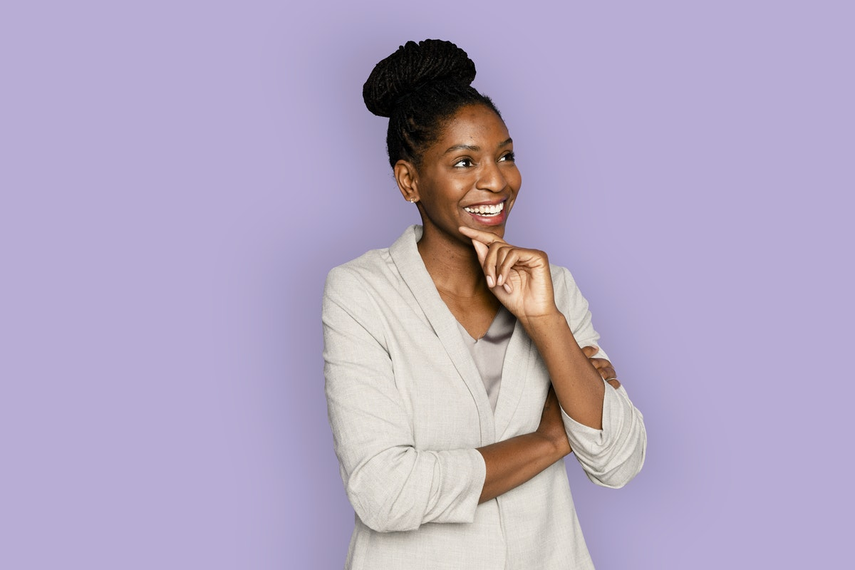 African-American woman standing and smiling with her hand on her chin in front of a purple background