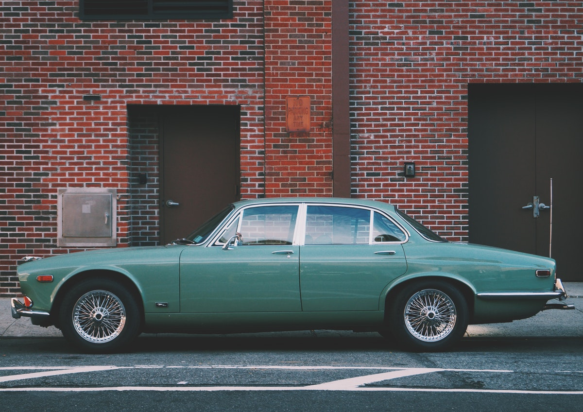 Old green muscle car parked outside red brick wall