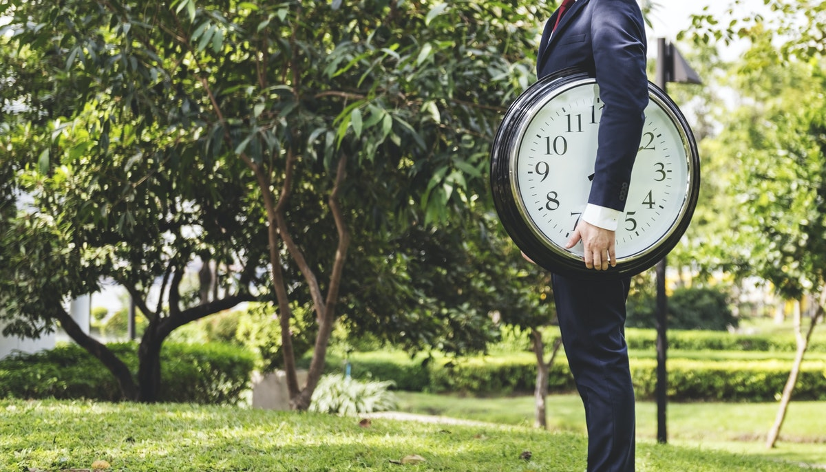 man in dark suit holding an oversized clock under one arm standing in a green field with trees