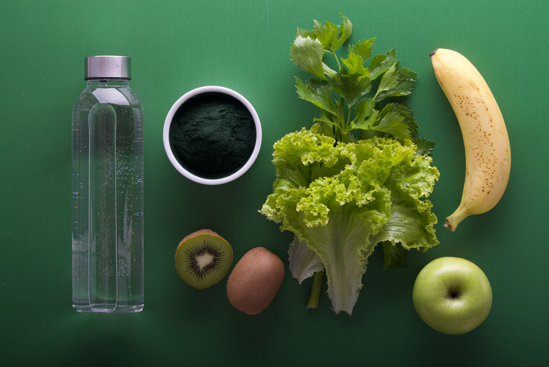 Top view of a bottle, greens and fruits