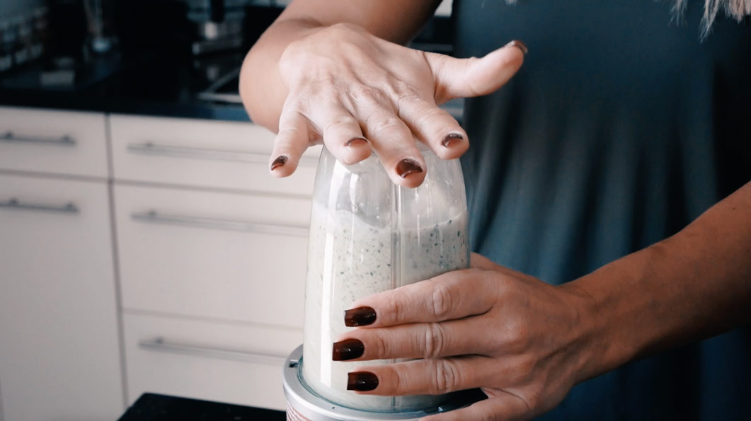 A woman prepares a protein shake in a blender