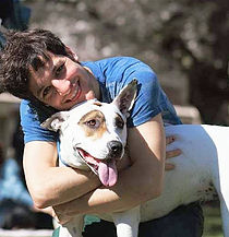 man in blue shirt hugging dog with mouth open