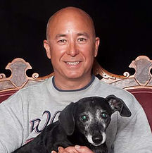 man smiling holding small black dog with gray face