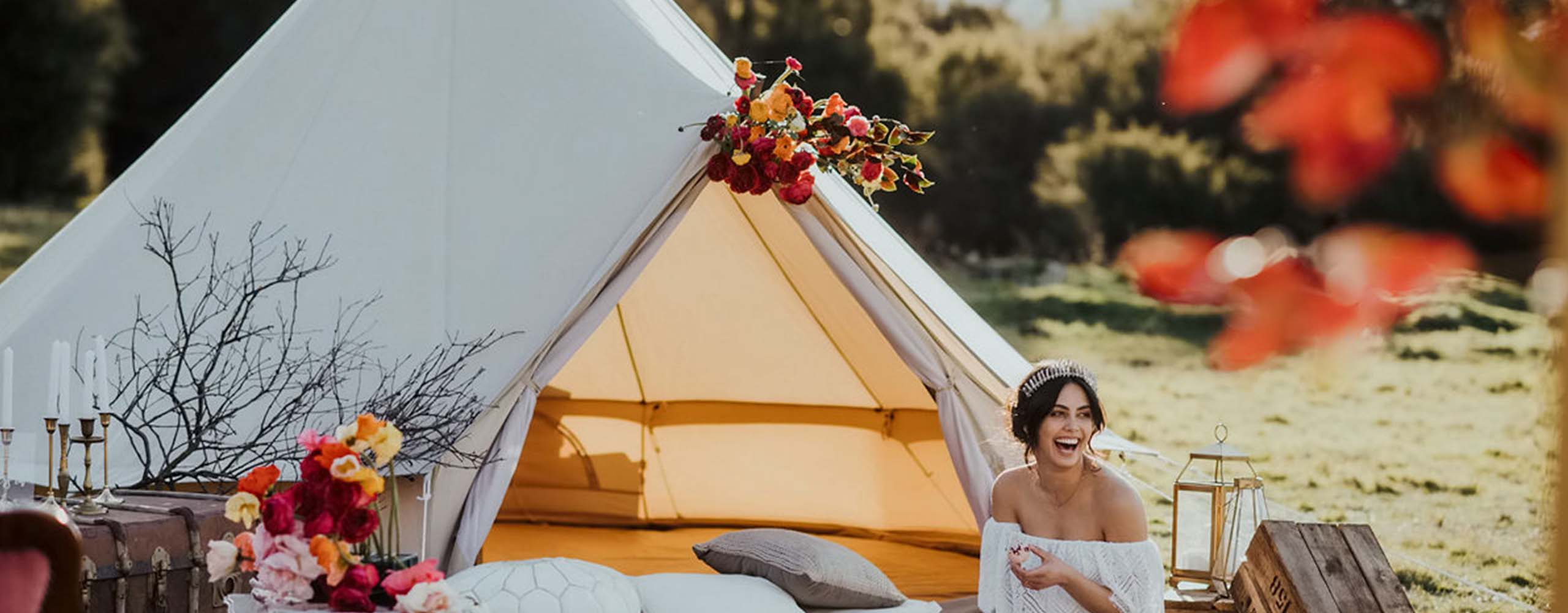 Glamping — styled glamping tent with florals and wedding gowns