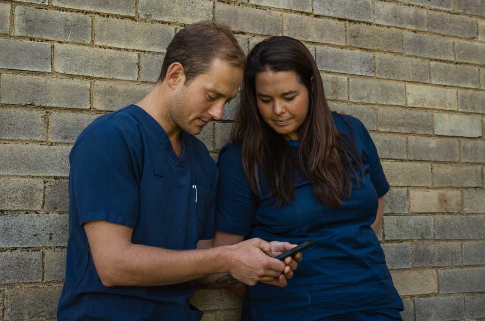 Male and female nurse looking at a phone application