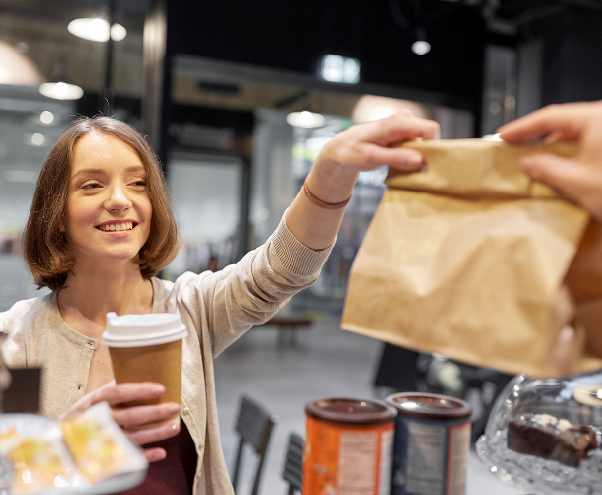 A young female customer grabbing her order from a cafe while smiling, to represent how Spot Parking is supporting local businesses
