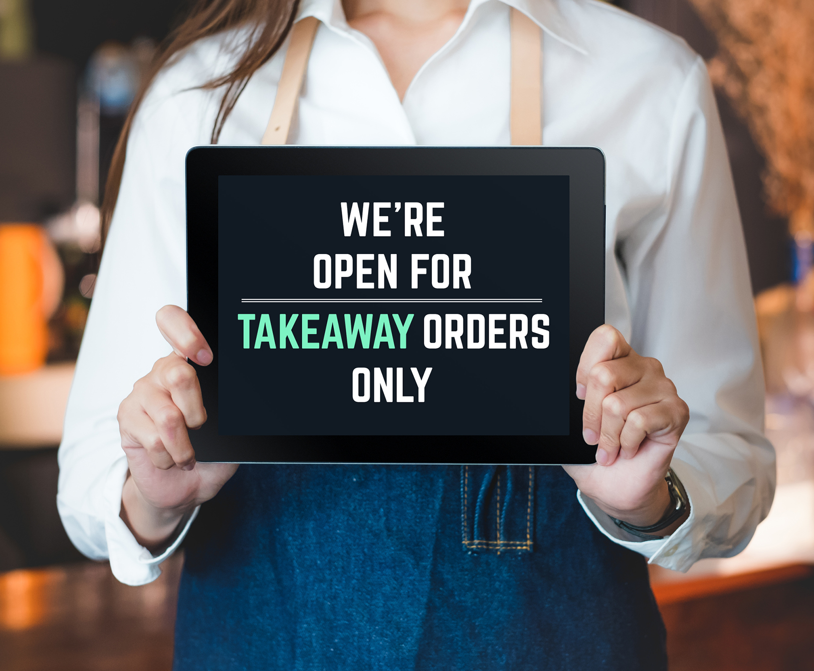 A young female from a cafe holding an Ipad that displays an 'open for takeaway orders' sign