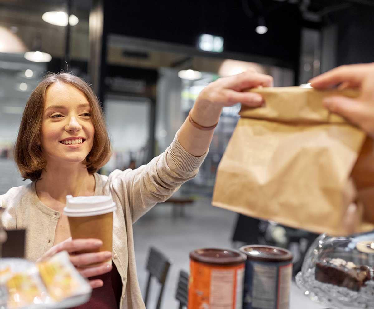Female cafe customer holding coffee receiving takeaway order in paper bag
