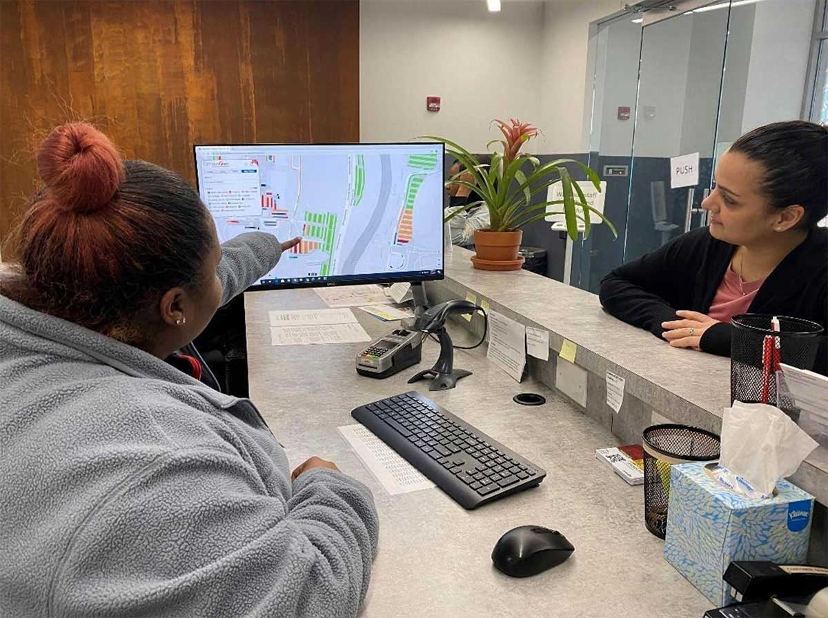 Customer service showing woman Spot Campus on computer monitor
