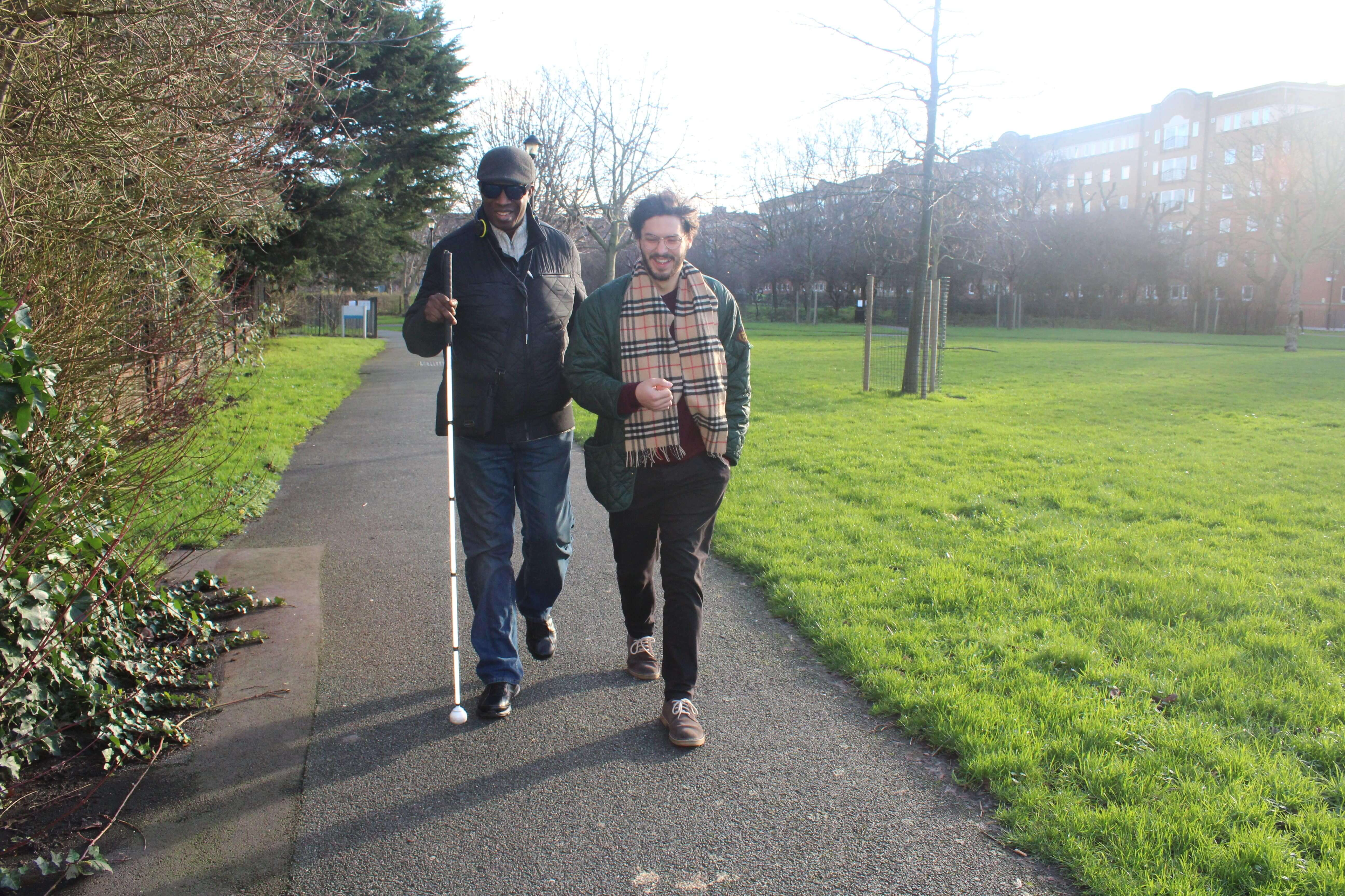 Visually impaired person walks with a volunteer