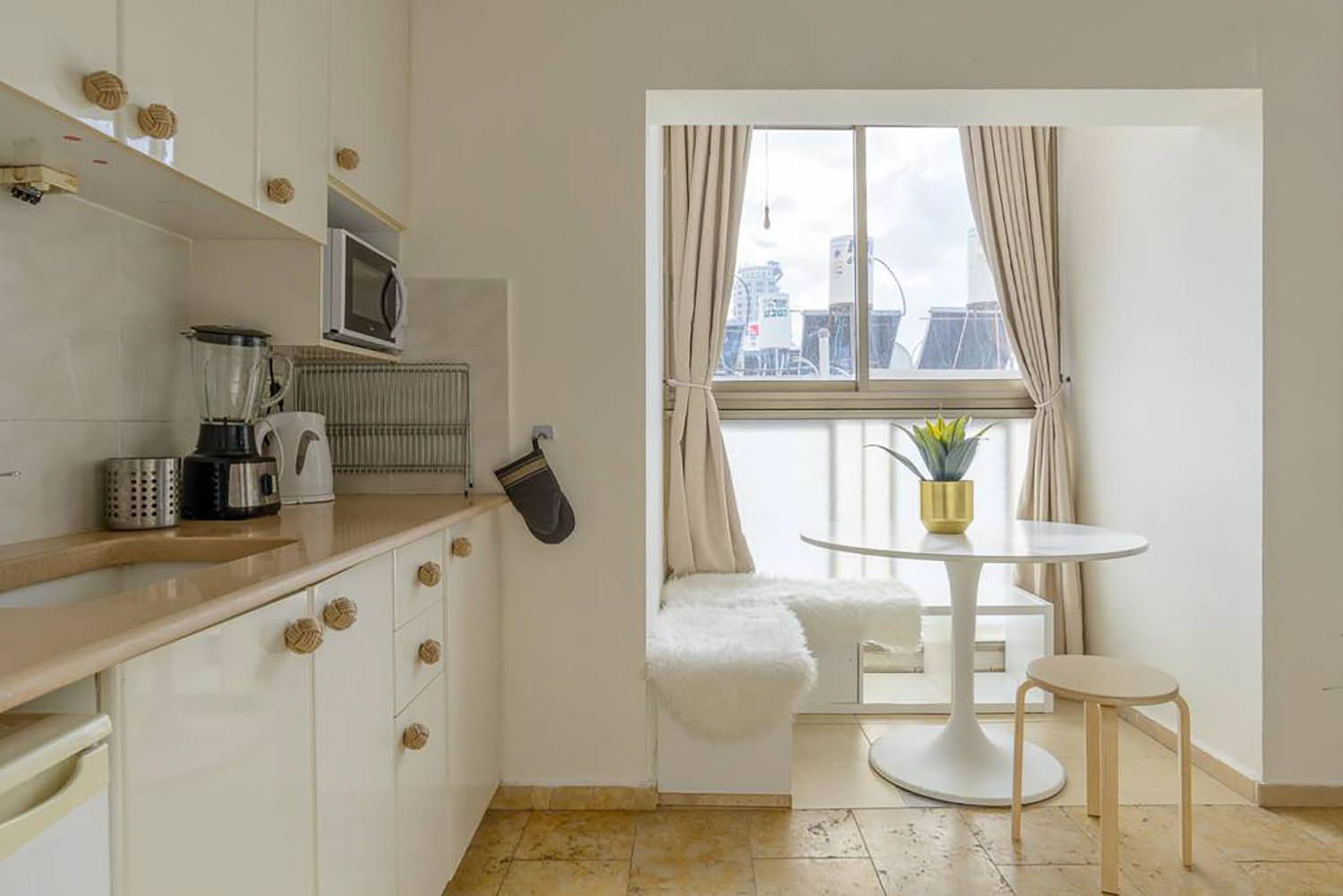 White and beige kitchen with dining nook made out of Ikea shelves. There are a white round table and a plant on top of it.