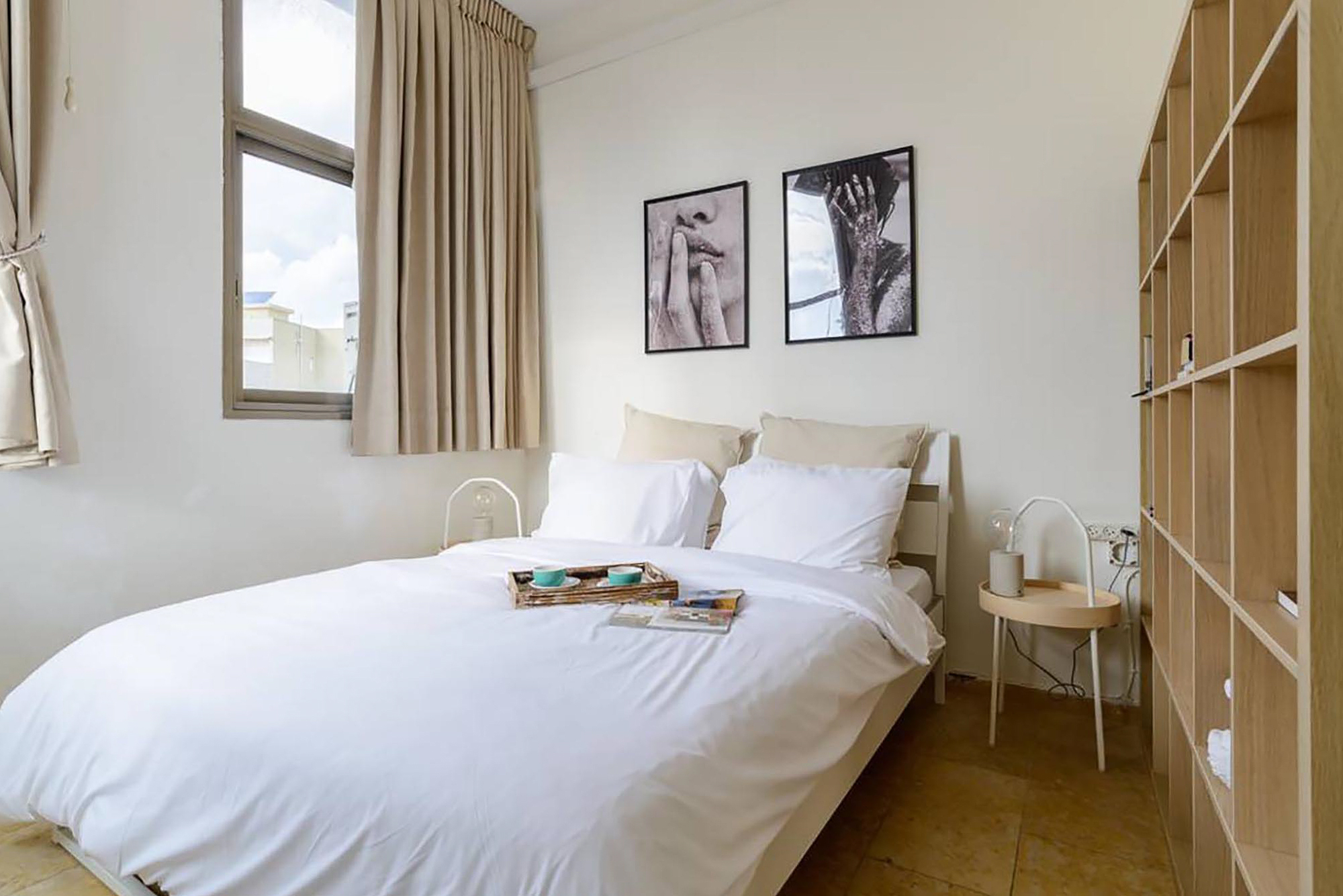 Minimal white bedroom with two black and white paintings on top of it. Round wood side tables and three big windows with a view of Ben Yehuda Street in Tel Aviv.