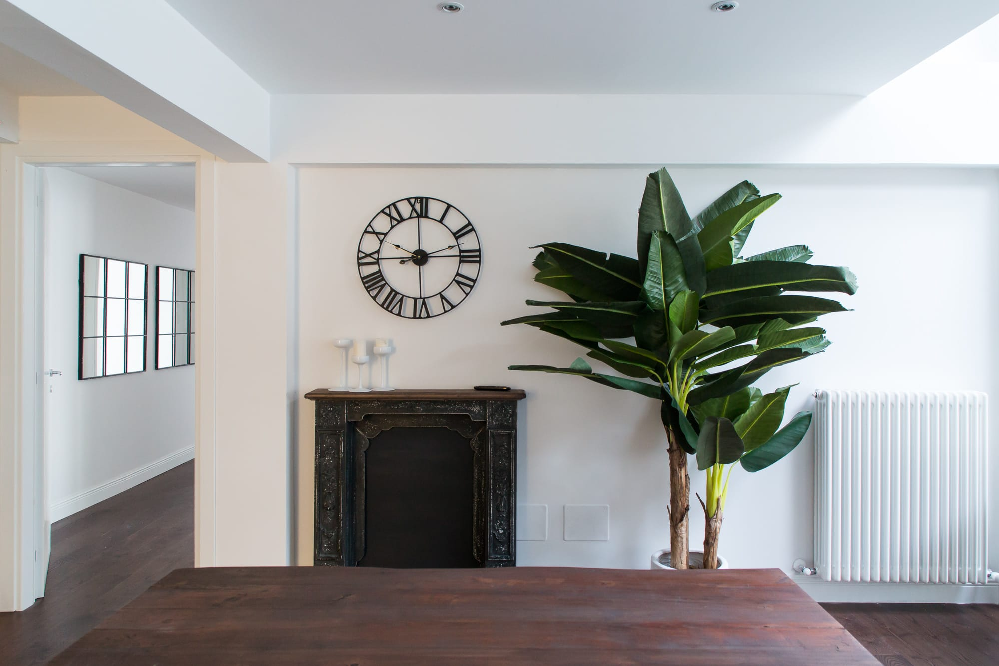 Vintage fireplace with a banana tree on the right side, a metal frame watch on the wall, and some minimal industrial mirrors on the left side of the wall.