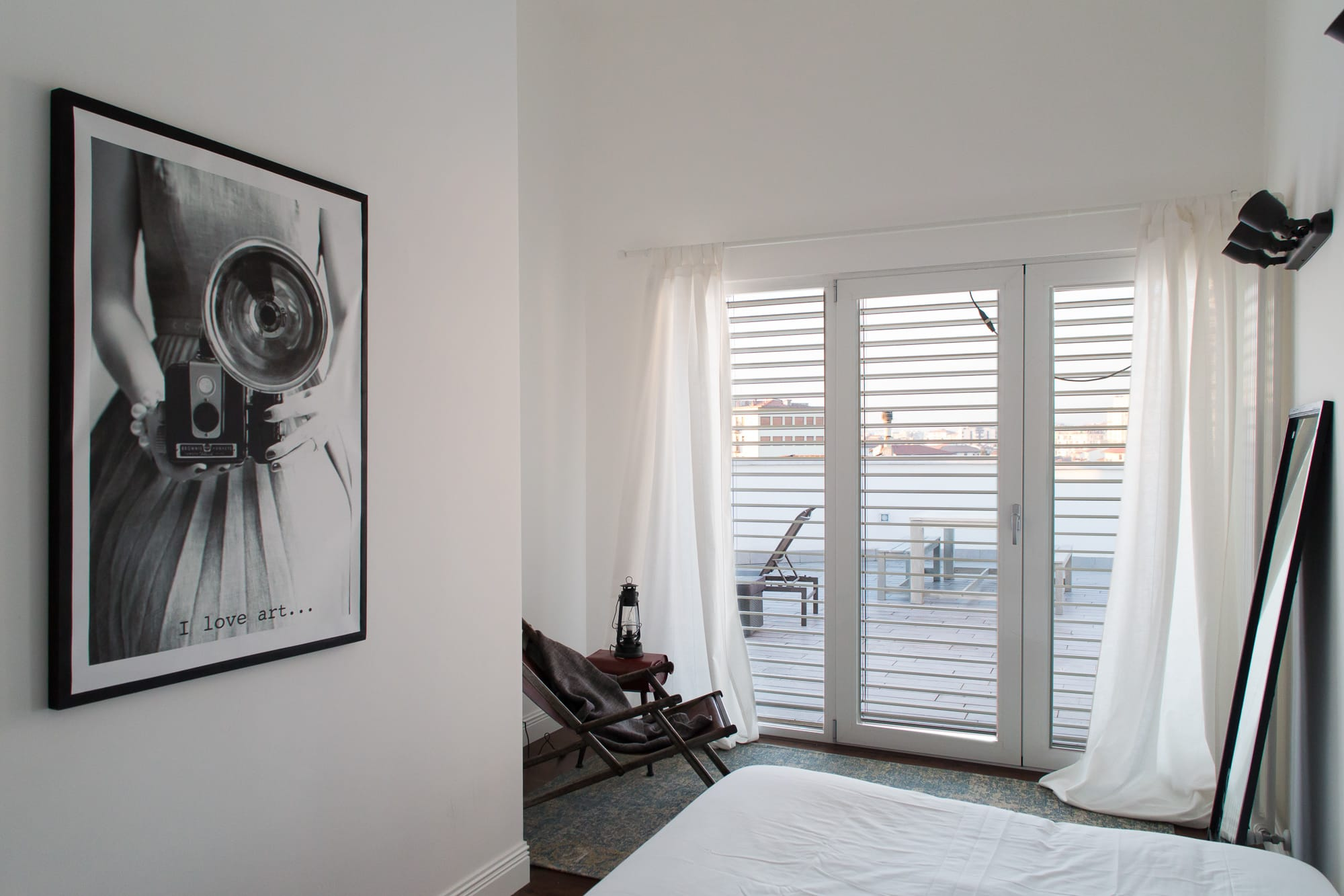 Vintage black and white painting in a white bedroom with wide window and leather lounge chair.