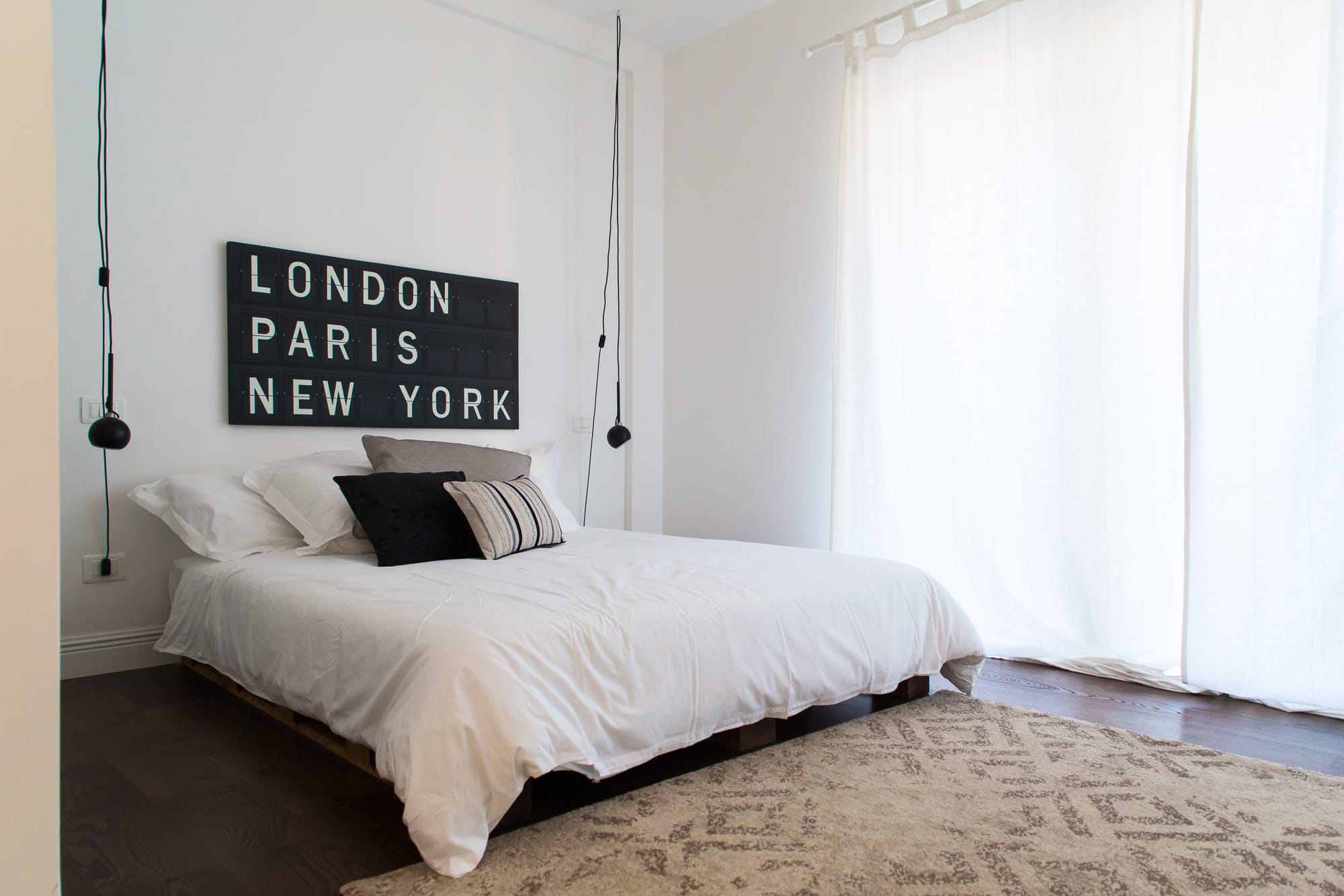 "Minimal design bedroom with a bed installed on a pallet frame. One single side lamps falling on the sides of the bed. One large painting with the sentence ""LONDON PARIS NEW YORK."""