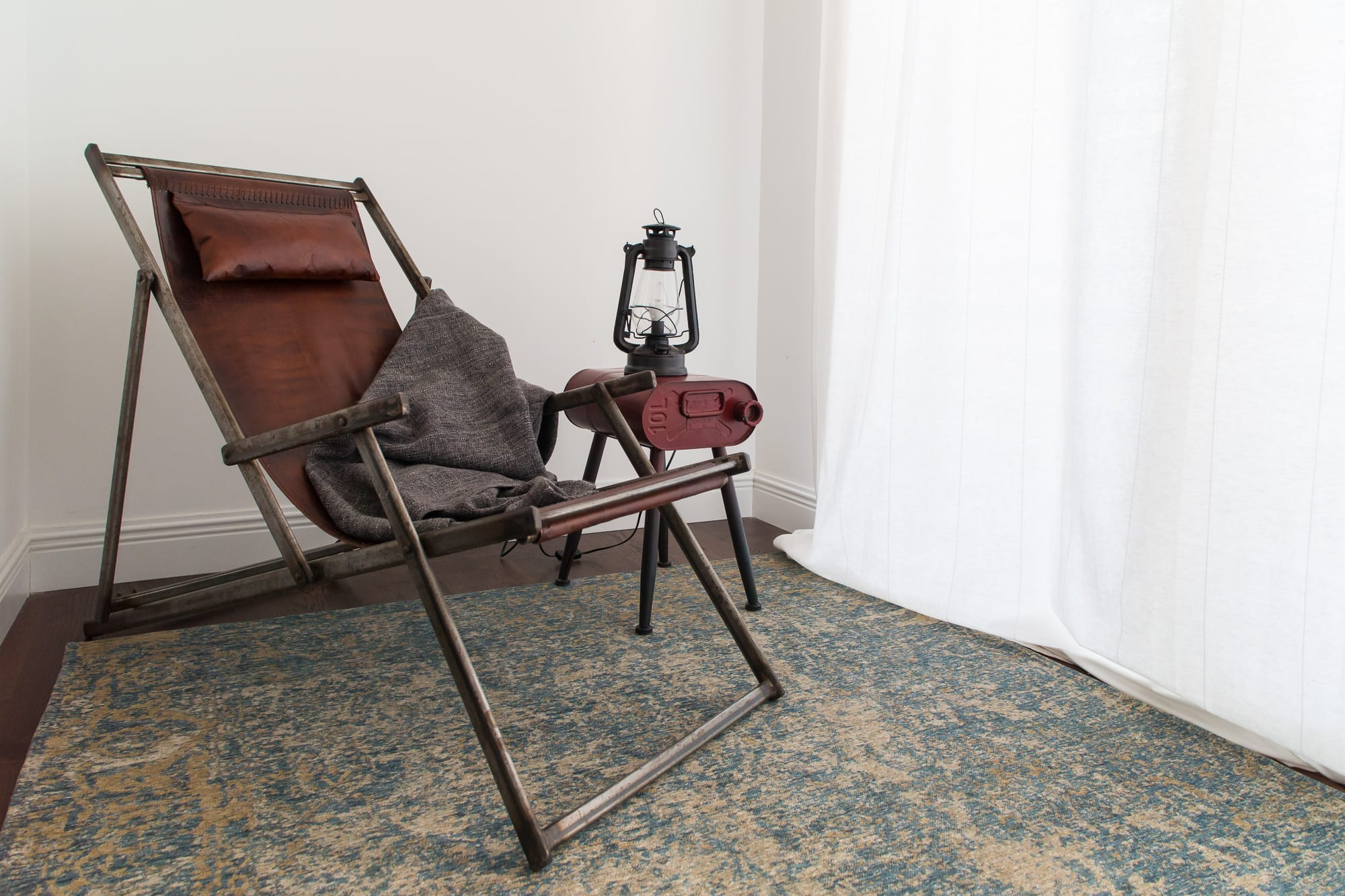 Leather and metal lounge chair on a blue abstract rug with an industrial side table.