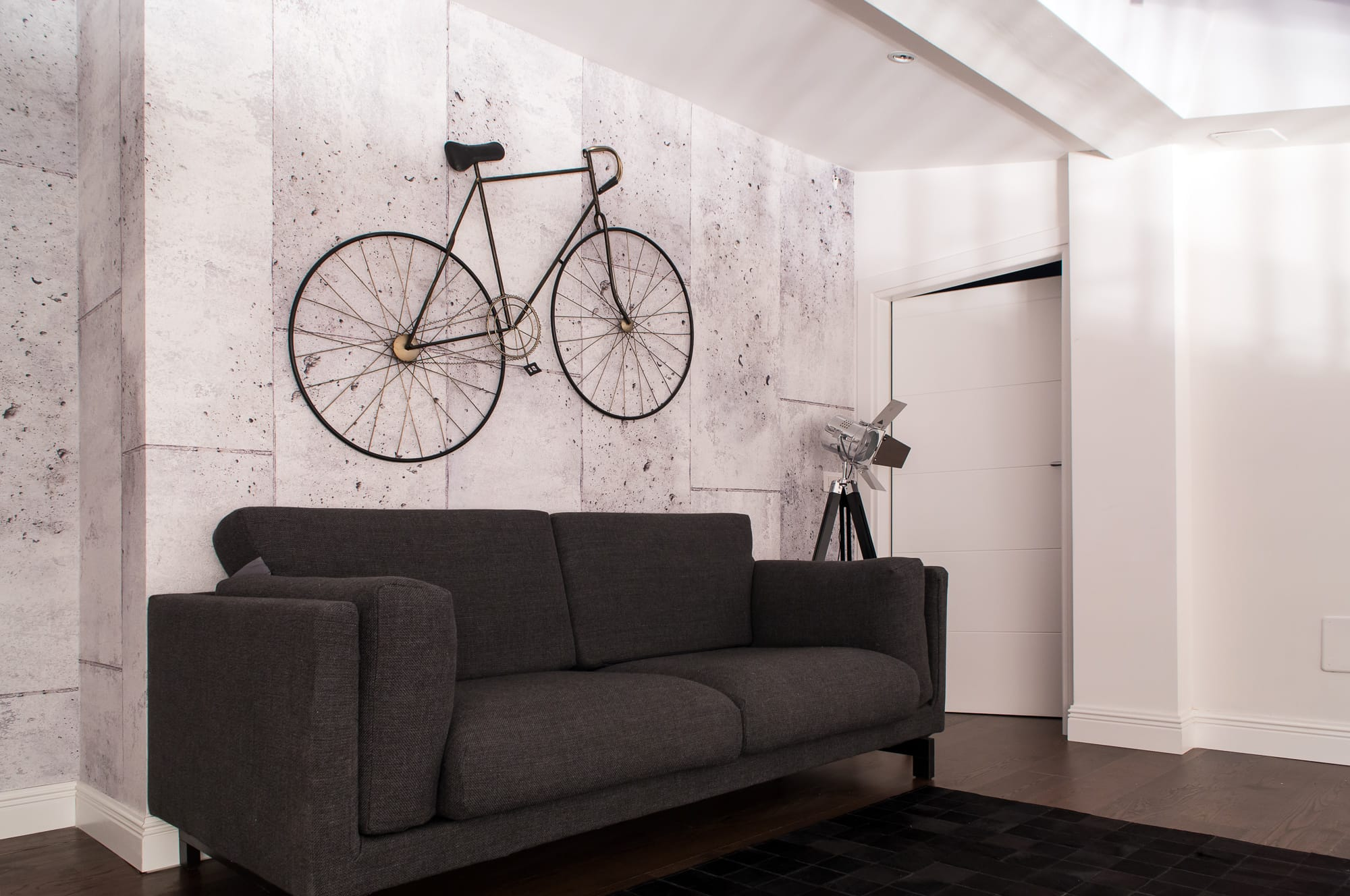 Gray concrete tiles on the wall and a gray couch under it. We see a leather rug on the floor made from patches and a vintage metal frame bike hanging on top of the sofa.