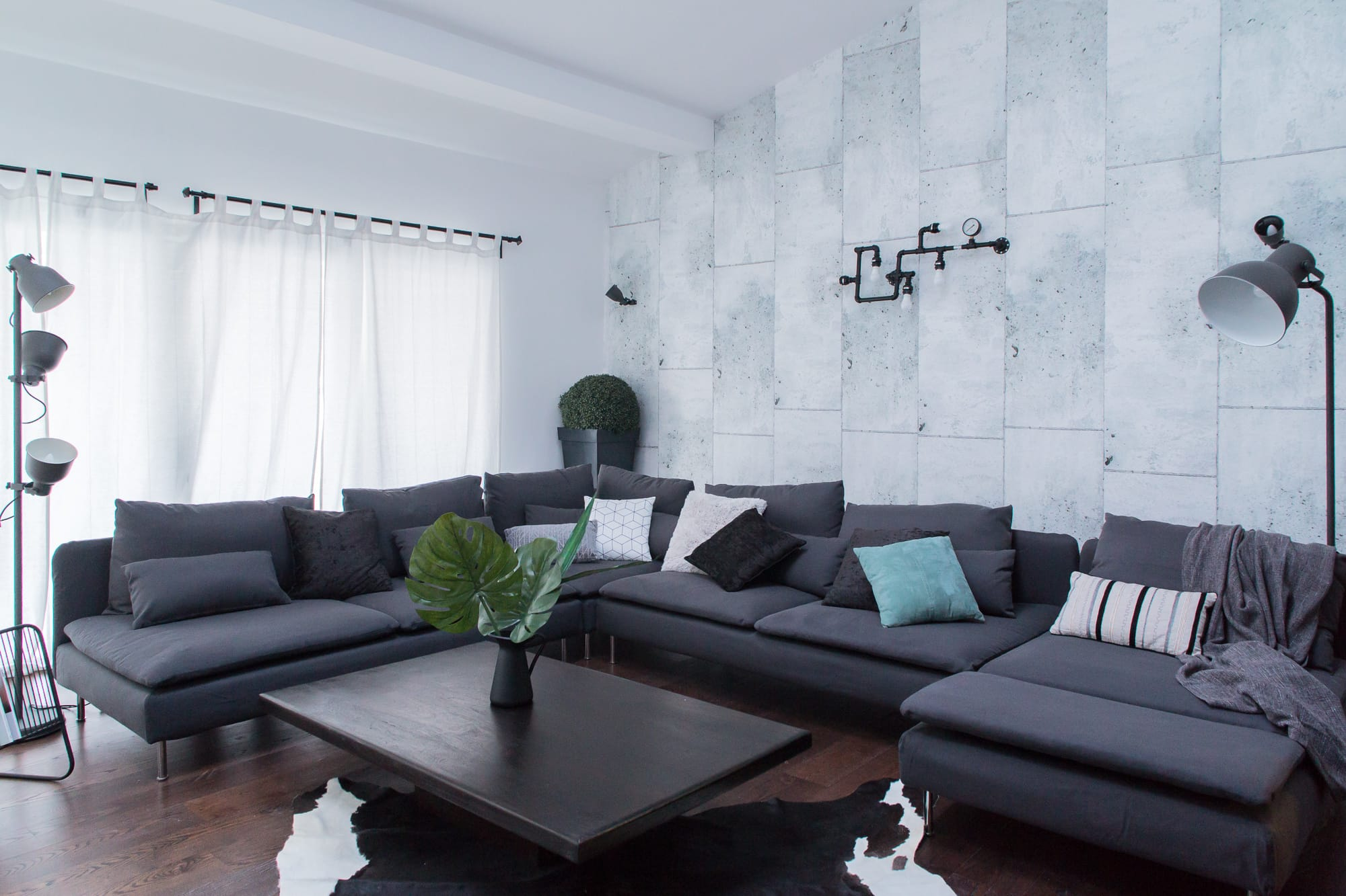 Gray concrete tiles and a white Soderhamn Ikea couch in a U shape and colorful throw pillows on top of it. There is a dark brown coffee table in front of the sofa and two light fixtures on the couch's side.