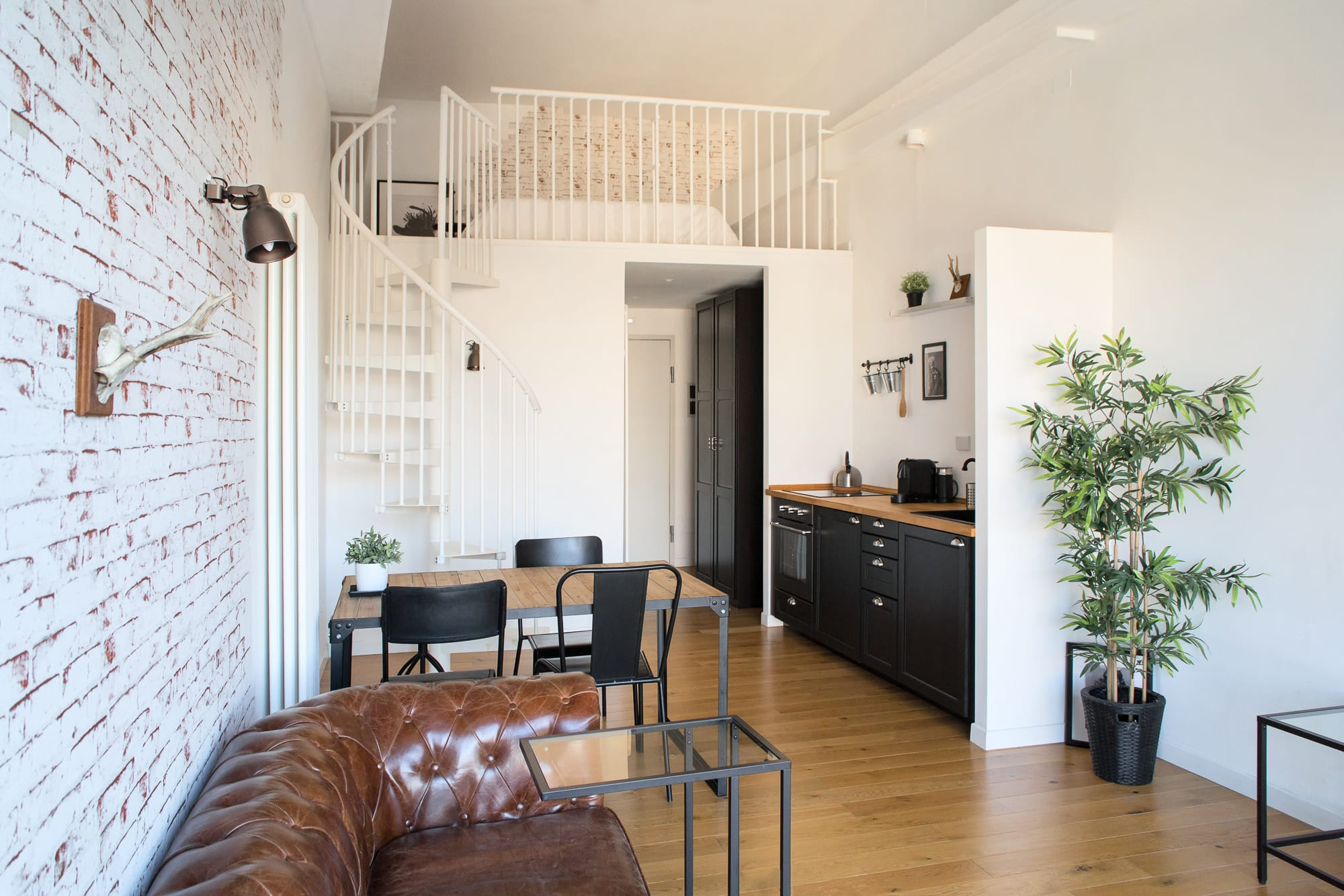 Industrial living room with black kitchen and metal frame dining table. The apartment is divided into two floors, and there are some white stairs on the left side close to a vintage leather couch.