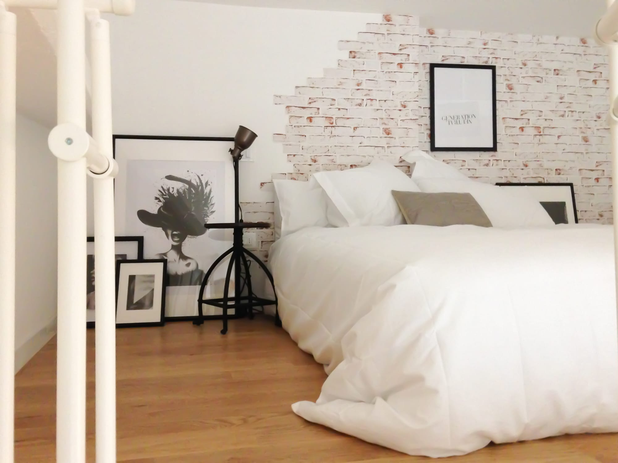 Minimal bed on pallets with brick wallpaper on the back and minimal frames on the floor. As side tables, there are two stools with a light fixture on top of it.