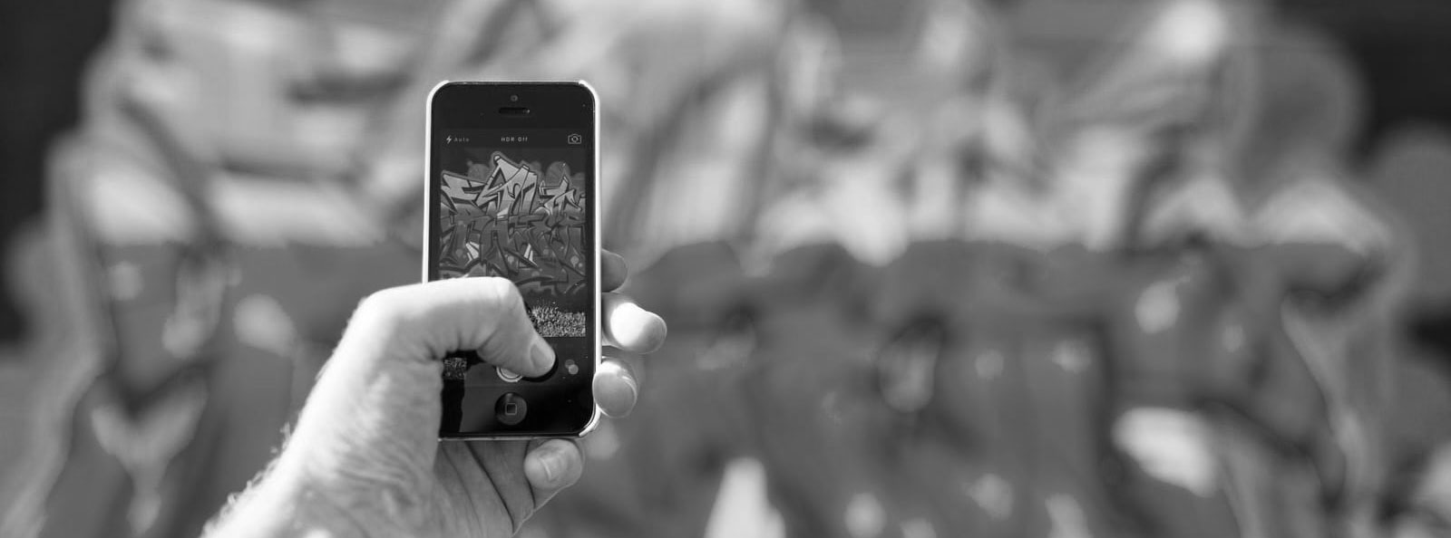 An individual clicking a photo of graffiti on the wall through his mobile