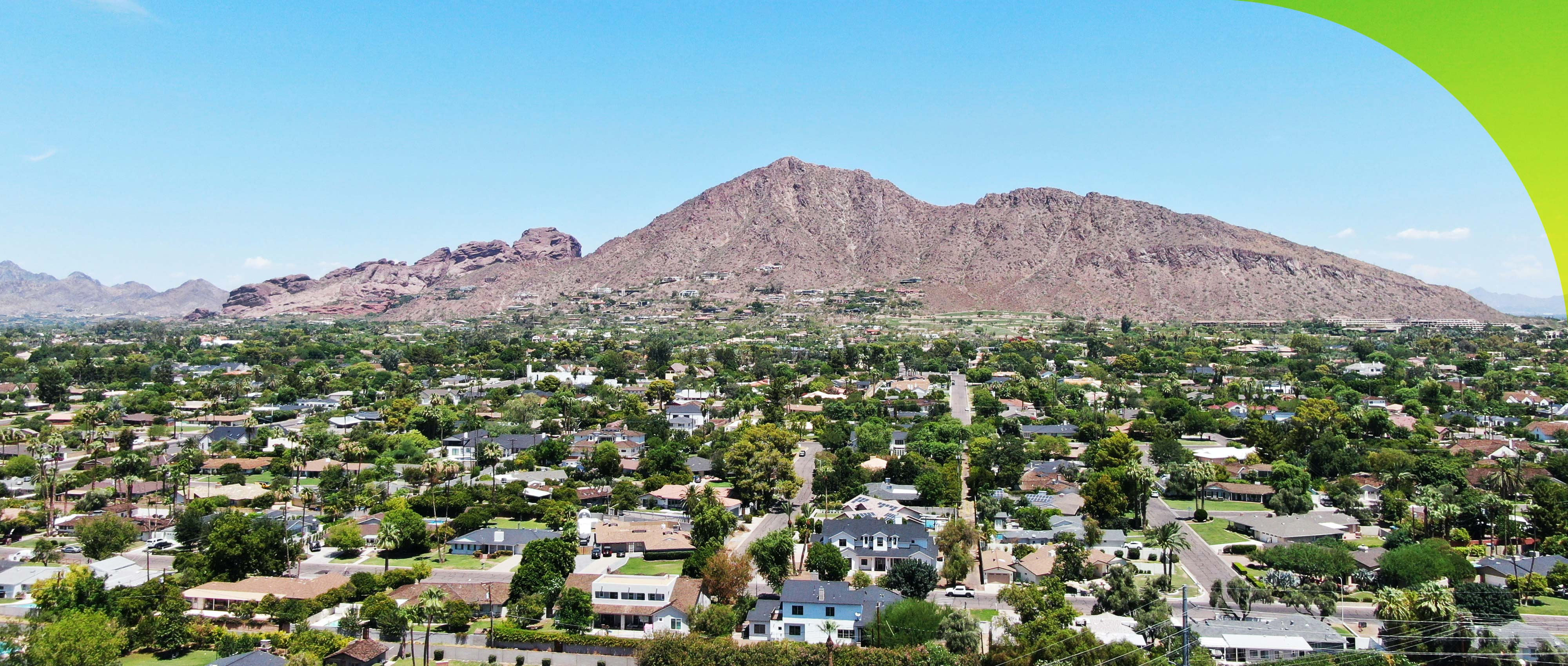 zoomed out shot of neighborhood in front of mountain range
