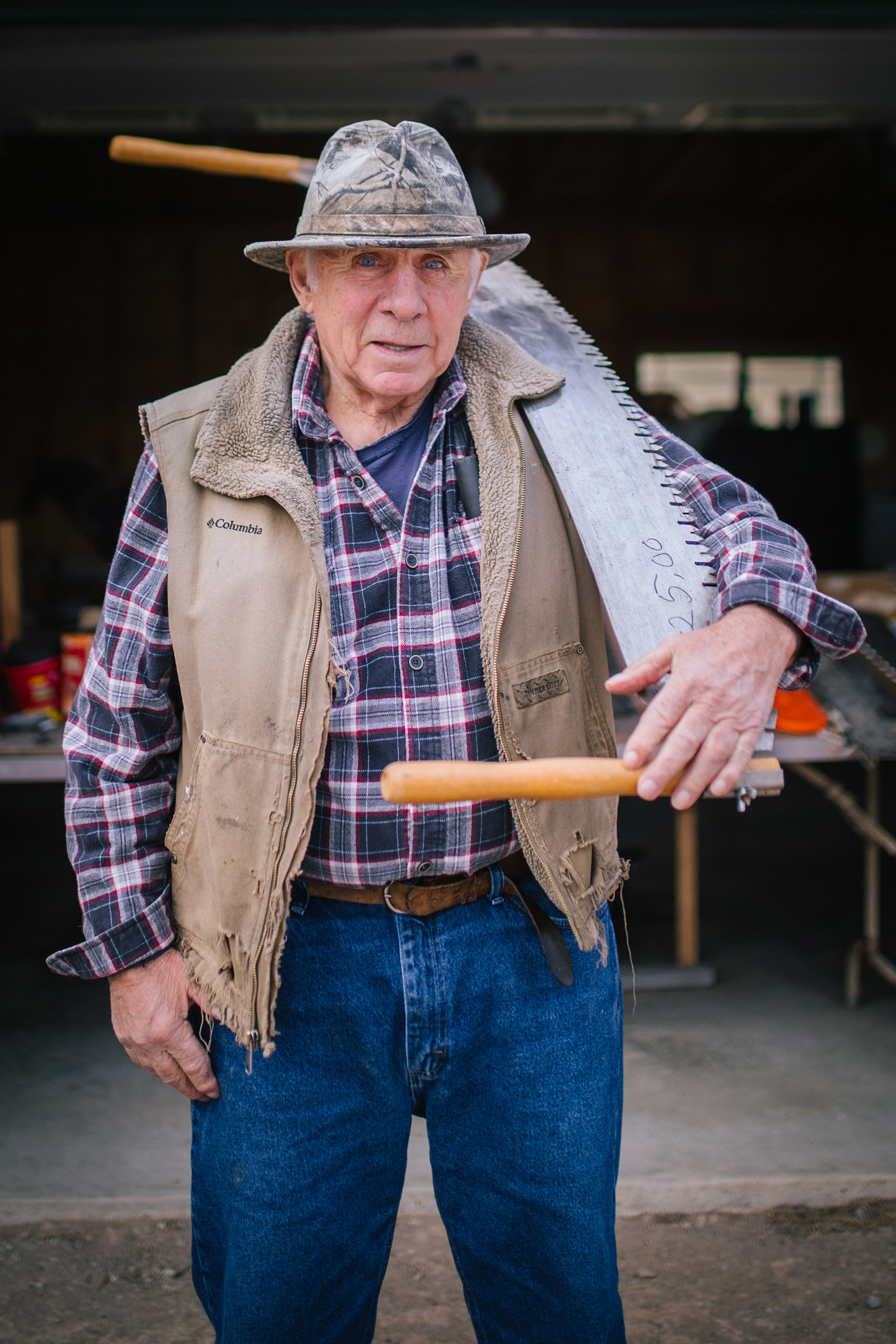 In this Montana photography session, Phil Crist poses in front of his workshop with one of his saws.