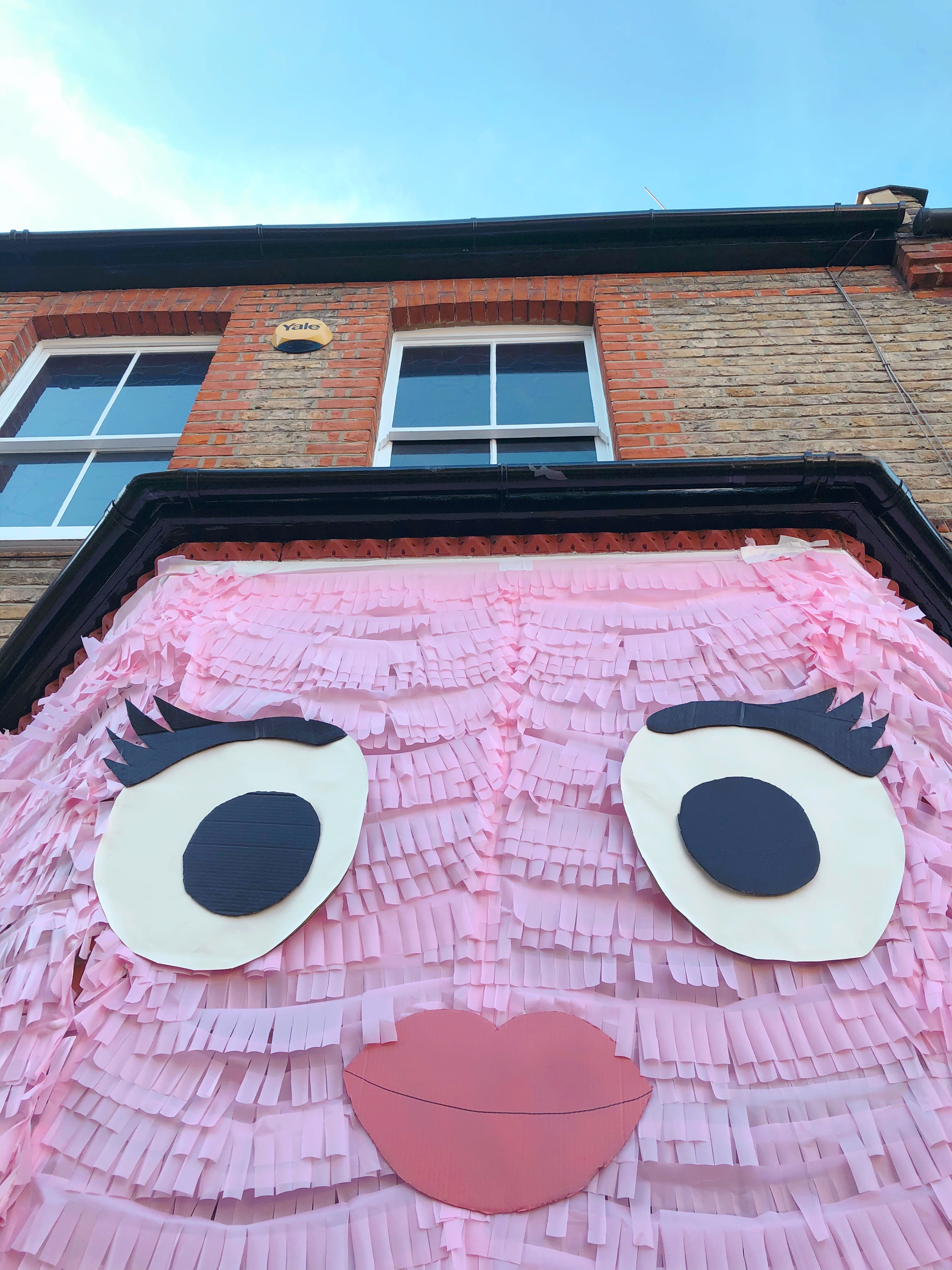 close up cute pink monster face house fringe piñata installation