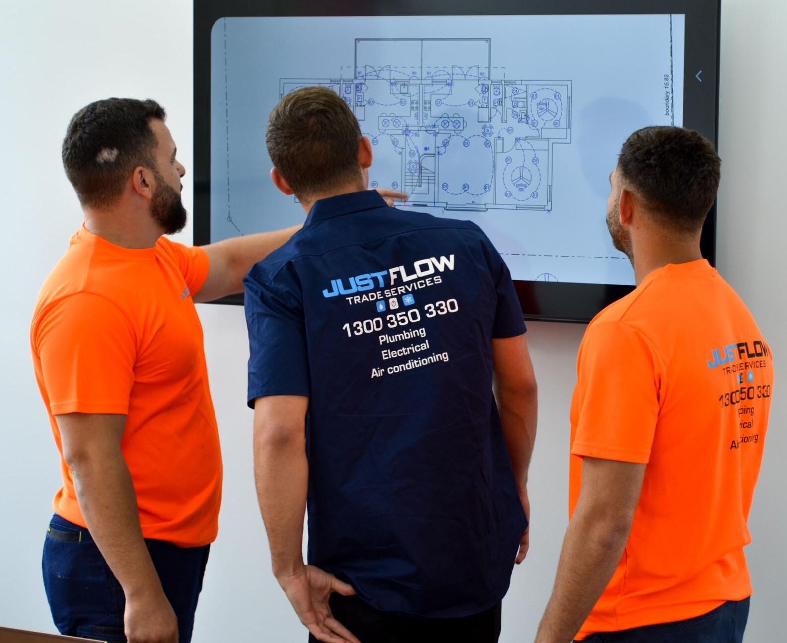 three professionals in electrical plumbing and air conditioning discussing a site plan on screen