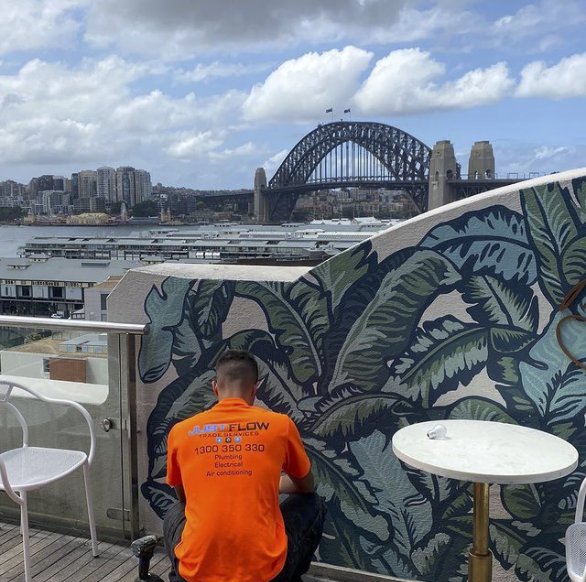 A Justflow electrician working on a power point in Sydney with view of harbour bridge in the background