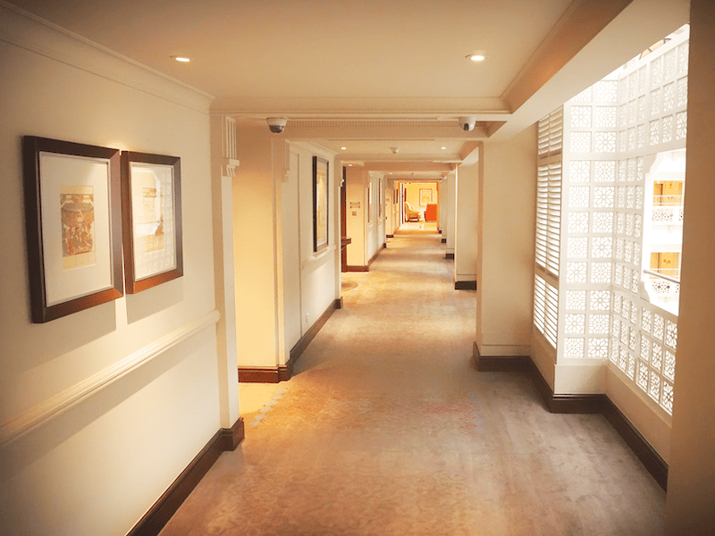 A hotel corridor with Toyama corridor and number panels