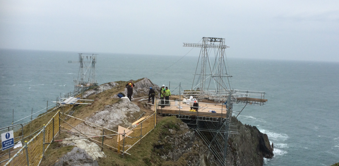 Our labours setting up a truss-supported stage by a cliff next to the ocean.