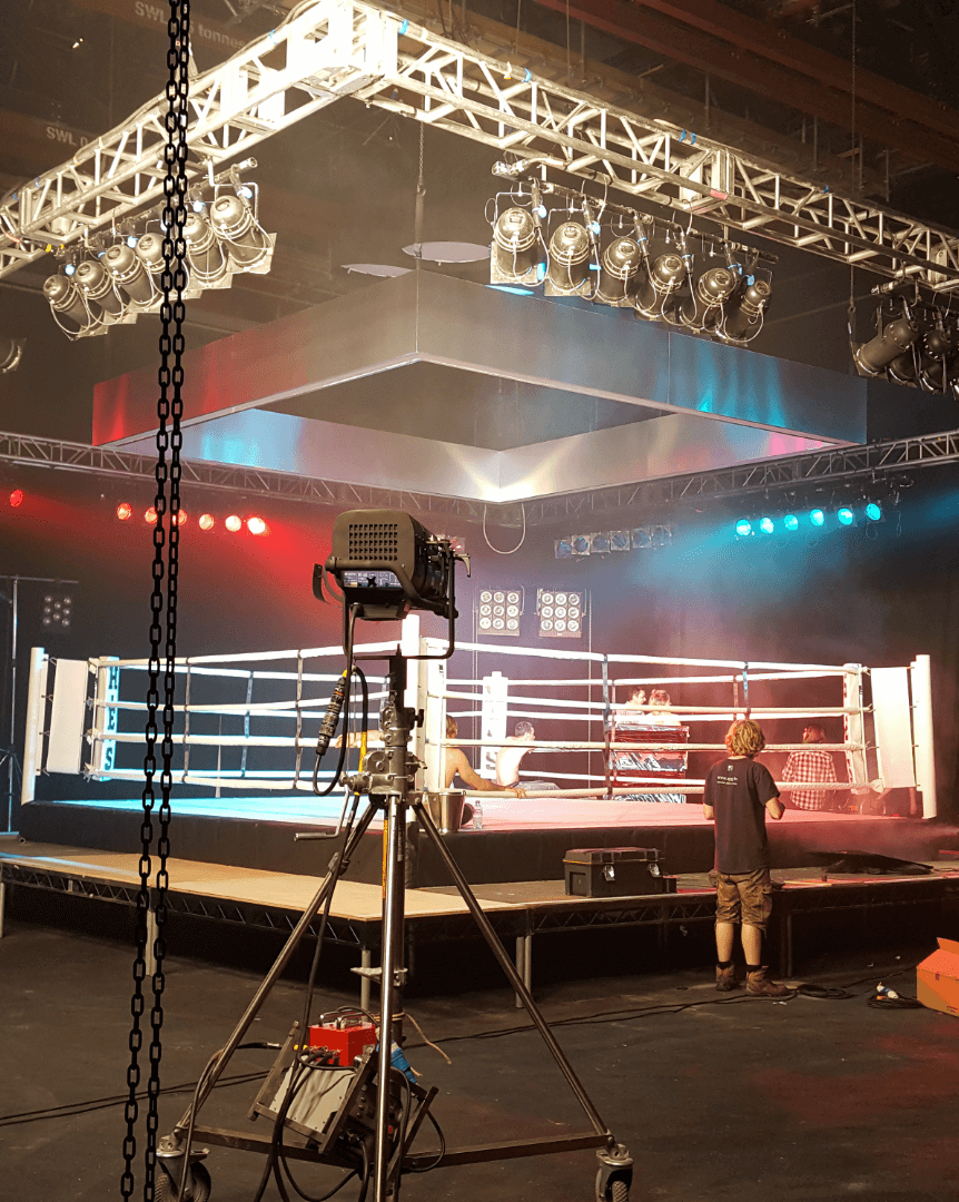 Aerial view of the stage lighting pipe grids set up above a boxing ring stage.
